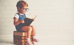 Klein meisje met bril zit al lezend op stapel boeken